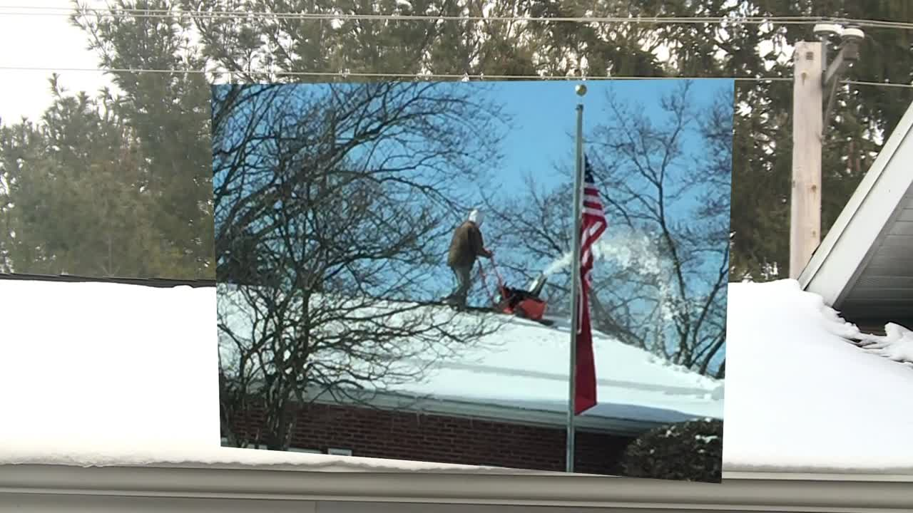 Man uses snowblower on funeral home roof